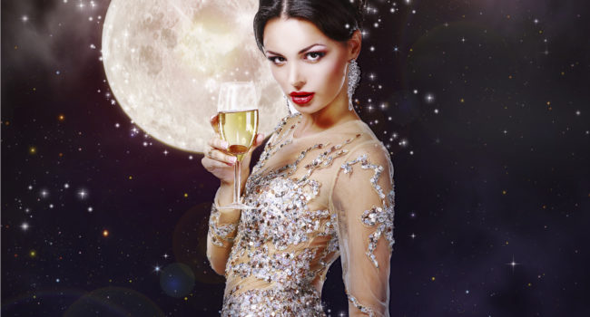 Romantic girl in the beautiful dress with a glass of champagne against the night sky with magical stars and moon.
