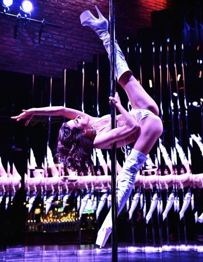 Nina side kicks holding the pole